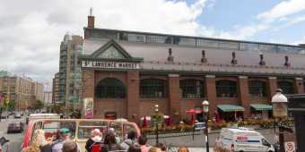 A view of the exterior of St Lawrence Market from a tour bus in summer
