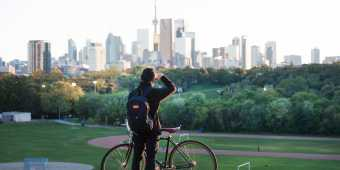 A person looks at the Toronto skyline from Riverdale Park in Toronto's east end