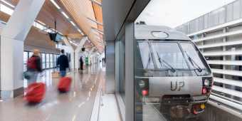 The UP Express train at Toronto Pearson station and passengers walking