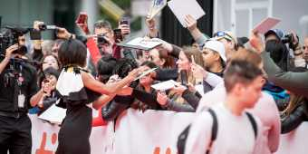An actress signs autographs for fans at the Toronto International Film Festival