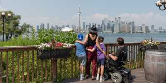 A family looks at the view of the Toronto skyline from Centre Island in summer
