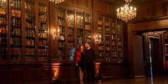 A couple explores the library at Casa Loma