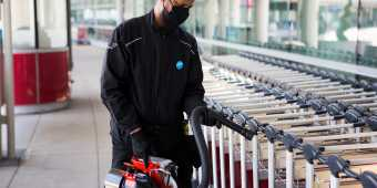 A staff member at Toronto Pearson disinfects baggage carts with a disinfecting fogging machine