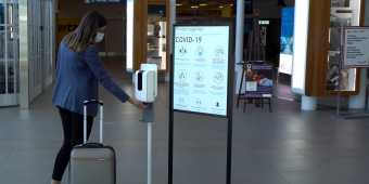A person using the hand sanitizer station at Billy Bishop Airport