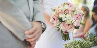 A couple getting married with a pink and white floral bouquet