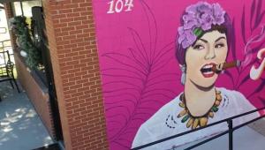 Hot pink mural of young woman smoking a cigar at Guava Tree Cuban Cafe & Cantina