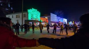 People take part in a community round dance in front of colourfully lit buildings during Holiday Alley 2018 in Selkirk, Manitoba