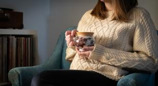 A woman in a white knit-sweater holds a hand-made ceramic mug while sitting in a blue chair