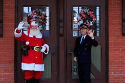 Santa Claus and the Polar Express train conductor waving in front of large brown doors