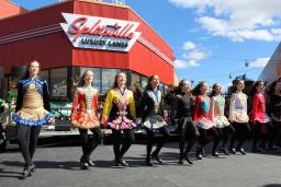 A line of Irish step dancers outside a bowling alley at Patriot Place