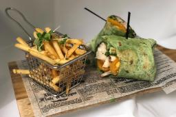 French fries served in a basket next to a chicken wrap.