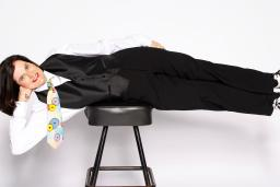 Paula Poundstone laying cross a chair in front of a white wall.