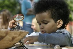 Child with a magnifying glass at the Roger Williams Park Zoo