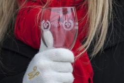 A woman wearing a red scarf and white gloves holding a wine glass.