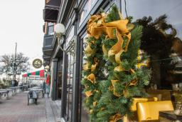 Holiday wreath with gold ribbons hanging on a reflective window