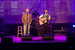Two actors portraying Simon and Garfunkel on stage singing into microphones.