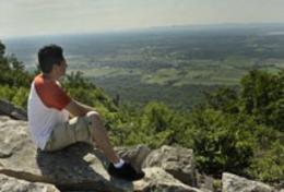 Man Sitting On Cliff Enjoying The View