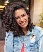 Photo of Jessica Serna, woman wearing a denim jacket with curly brown hair smiling at the camera