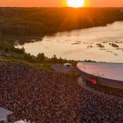 Aerial shot of Lakeview Amphitheater, large crowd infront of amphitheater set on the shores of Onondaga Lake, a fiery orange sunset can be seen in the horizon