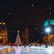 Glowing christmas tree set behind people skating at Clinton Square ice rink at night