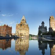 Beautiful Sun Shines Down on Historic Downtown Buildings and Calm Water