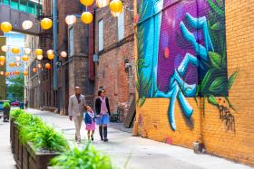 Father, mother, and daughter walking past a mural and the Porch off Calhoun in downtown Fort Wayne, Indiana.
