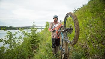 A mountain biker shows the mud on his tires from biking the trails.