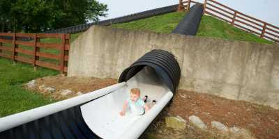 Young boy sliding down head first on a hill slide at Huber's Orchard, Winery & Vineyards