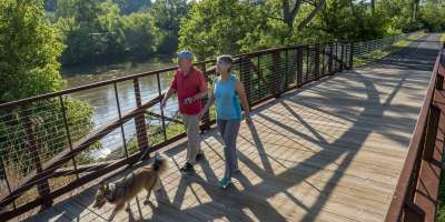 Couple walking dog along French Broad River Greenway