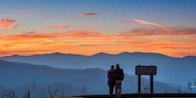 A couple enjoys a mountain vista on the Blue Ridge Parkway near Asheville, NC