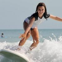 Young girl surfing of the coast of Daytona Beach