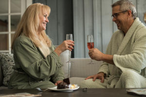 Couple drinking wine in bed an breakfast suite