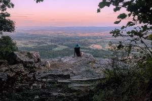 Hiker sitting on rock overlooking valley on Flat Rock Trail