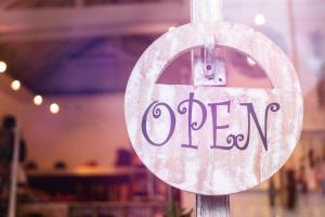 "An ""OPEN"" sign hangs on a hook inside a window of a Cumberland Valley small business."