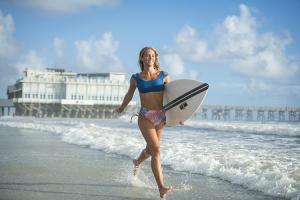 A surfer running on the beach in Daytona Beach, Florida