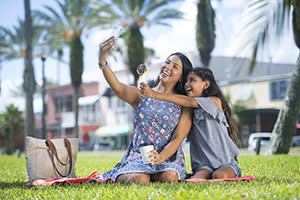 Smiling mother and daughter posing for a selfie in Daytona Beach