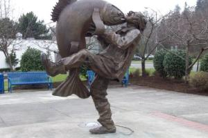 Big Catch Plaza sculpture in Des Moines Washington of Giant Fish and Man Kissing