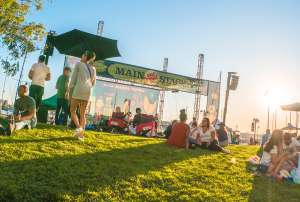 Oakland visitors sitting on the lawn in front of the Main Stage