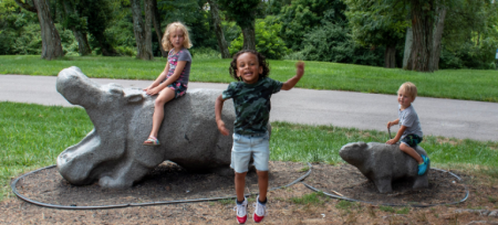 three children enjoying playing on concrete hippos at Florence nature park in Florence ky