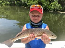 Little boy holding a redfish