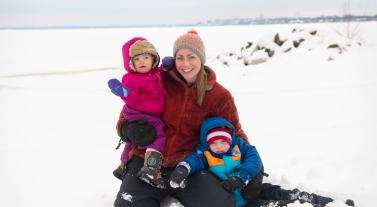 A mother and her two children play in the snow at Olbrich Park