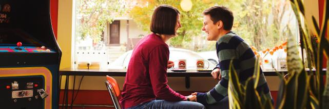 A couple laughs and holds hands at Rainbow Bakery in Bloomington, IN