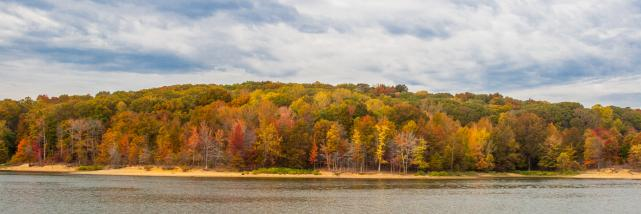View of the water rippling at Lake Monroe surrounded by fall foliage