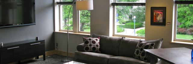Living room space with a couch and coffee table at Suites at 118