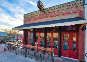 Photo of front of Cadillac Pizza Pub showing outdoor bar and patio, blue sky