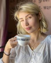 writer Natalie La Flare holding coffee cup and winking at camera