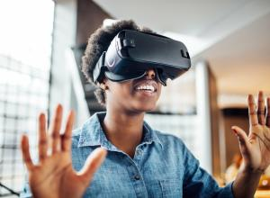 Smiling african-american woman wearing virtual reality headset in office. Young female at startup using VR goggles.