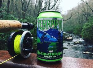 A can of Terrapin beer alongside a fishing reel with a stream in the background