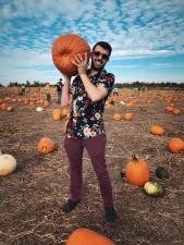 Man holding a big pumpkin over his shoulder at Hubers Pumpking Patch