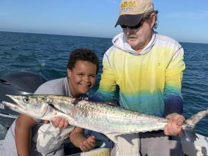 Fishing: Capt. Van Hubbard and young fisherman holding a King Mackerel